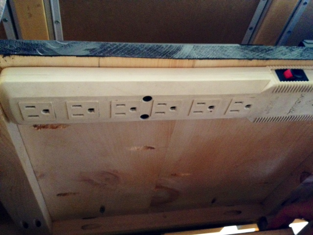 The view of underneath the shelf in the cabinet showing the power bar.