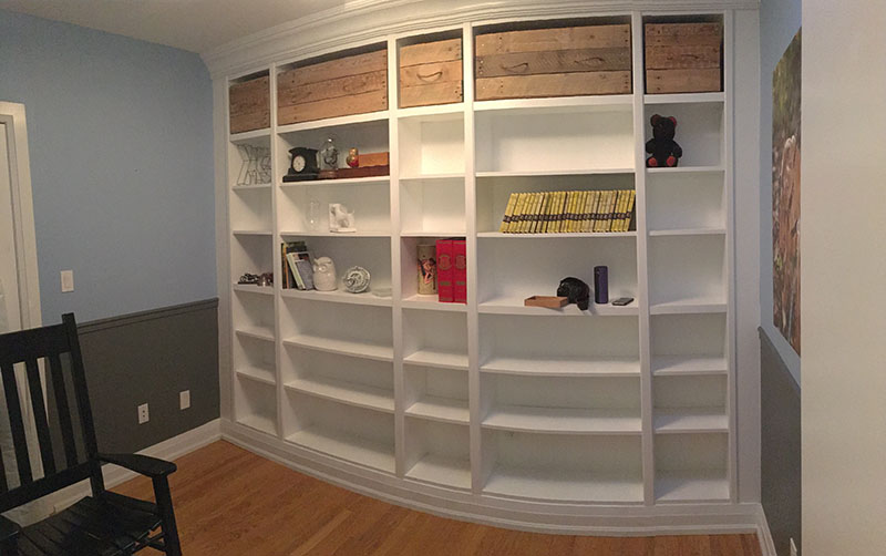 Wall of Bookcases (Pardon the curve, its a tiny room, and a panoramic was needed to capture the whole thing)